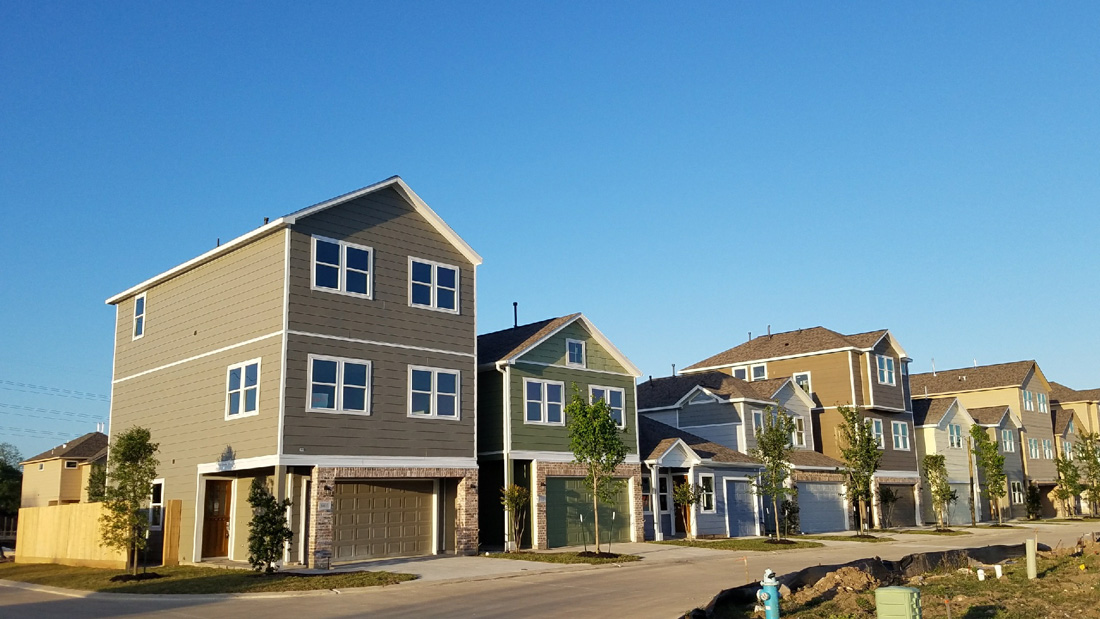 Oaks Of Lawndale by Drake Homes Inc. Under a blue Texas Sky.